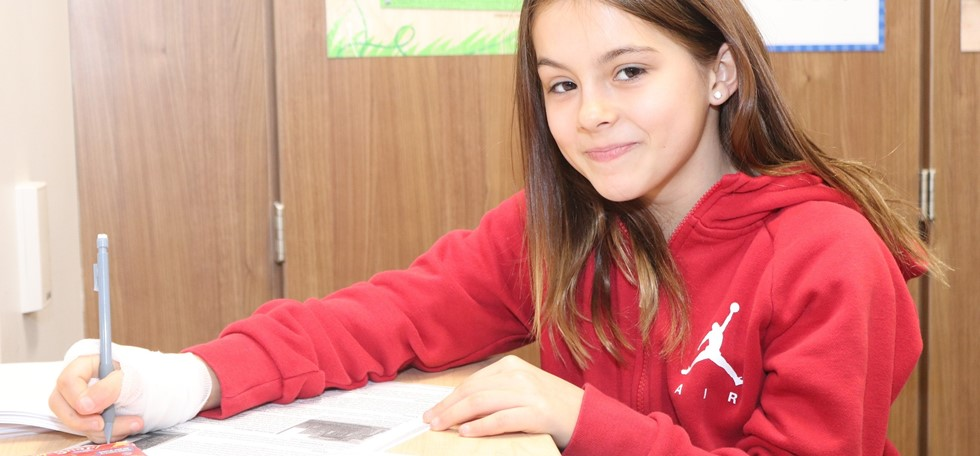 Struble student smiling while writing at the desk