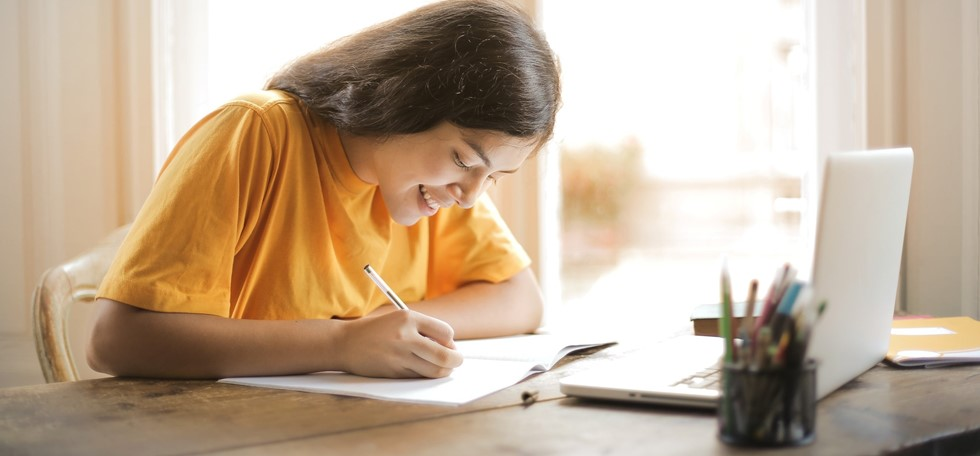 Girl writing in front of a laptop
